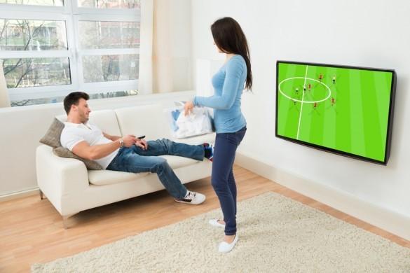 Woman Looking At Man Watching Football Match On Television
